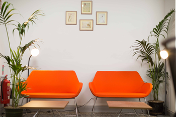 Two orange armchairs in the Kilrush Digital Hub with four pictures on the wall behind them